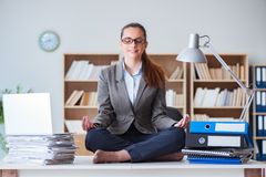 The businesswoman meditating in the office. Businesswoman meditating in the office Royalty Free Stock Image