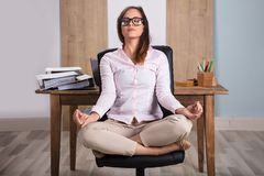 Businesswoman Meditating In Office. Young Businesswoman Sitting On Chair Meditating In Office Stock Images