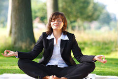 Businesswoman meditating outdoor in park Royalty Free Stock Photo