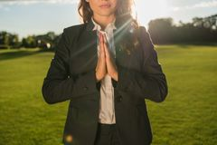 Businesswoman meditating in park. Partial view of businesswoman in suit meditating in park Royalty Free Stock Photos