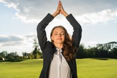 Businesswoman meditating in park. Portrait of smiling businesswoman meditating in park Royalty Free Stock Photos