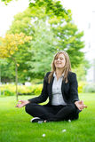 Businesswoman meditating and Yoga in a park Royalty Free Stock Images