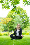 Businesswoman meditating and Yoga in a park Stock Photo