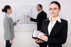 Businesswoman in a meeting. A young businesswomen participates at a meeting, at her workplace Royalty Free Stock Photos