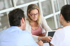 Businesswoman meeting a couple to sign a contract Stock Image