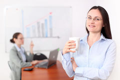 Businesswoman in a meeting room. A business women is holding a cup of coffee in a conference room Royalty Free Stock Photo