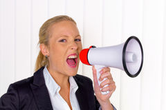 Businesswoman with megaphone. A young businesswoman with a megaphone makes an announcement Royalty Free Stock Photos