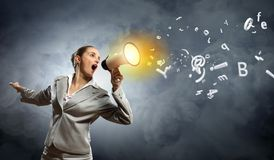 Businesswoman with megaphone. Businesswoman in grey suit screaming into megaphone Royalty Free Stock Photo