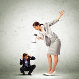 Businesswoman with megaphone. Angry businesswoman with megaphone shouting at colleague Royalty Free Stock Photo