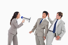 Businesswoman with megaphone yelling at colleagues. Against a white background Stock Images