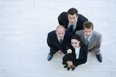 Businesswoman and men looking up and smiling Stock Images