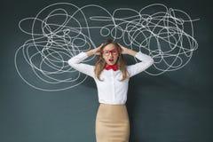 Businesswoman Mess on Blackboard. Portrait of confused businesswoman on blackboard Stock Photo