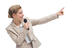 Businesswoman with microphone indicating something Royalty Free Stock Images