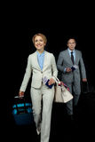 Businesswoman and middle aged businessman with suitcases ready to trip. On black Royalty Free Stock Images
