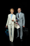 Businesswoman and middle aged businessman with suitcases ready to trip. On black Stock Photography