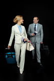 Businesswoman and middle aged businessman with suitcases ready to trip. On black Stock Image