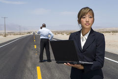 Businesswoman in middle of road in desert using laptop computer, man in background Royalty Free Stock Photos