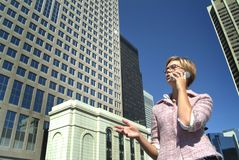 Businesswoman with mobile. Low angle view of young businesswoman with mobile telephone, high rise office buildings in background Royalty Free Stock Photography