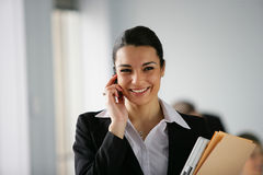 Businesswoman with mobile phone. Businesswoman talking on a mobile phone in the office Royalty Free Stock Image