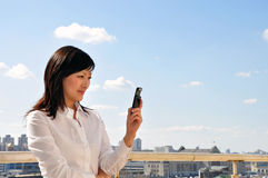 Businesswoman with mobile phone. Young businesswoman looking on the mobile phone in left hand, outside, space for copy and text Stock Photography