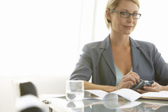 Businesswoman With Mobile Phone At Conference Table Royalty Free Stock Photos
