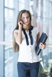 Businesswoman on mobile phone holding folder Royalty Free Stock Images