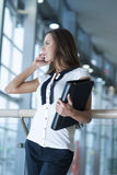 Businesswoman on mobile phone holding folder Stock Image