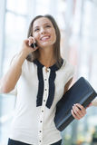 Businesswoman on mobile phone holding folder and smiling Stock Photo