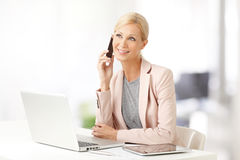 Businesswoman with mobile phone. Portrait of attractive sales woman making call while sitting at office in front of laptop and working Stock Photography