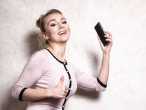 Businesswoman with mobile phone showing thumb up Stock Photos