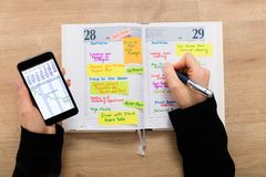 Businesswoman With Mobilephone Writing Schedule In Diary. High Angle View Of A Businesswoman Writing Schedule In Diary Using Mobilephone On Wooden Desk Stock Photos