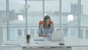 Businesswoman in modern office busy with paperwork, typing on laptop computer. 4K stock footage