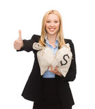 Businesswoman with money bags showing thumbs up Stock Images