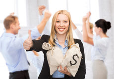 Businesswoman with money bags showing thumbs up Royalty Free Stock Image