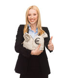 Businesswoman with money bags showing thumbs up Stock Photo