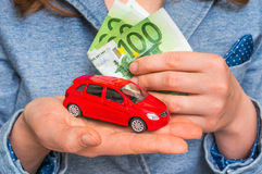 Businesswoman with money and toy red car in hands Stock Photo