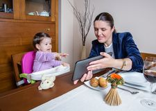 Businesswoman mother and baby girl looking tablet Royalty Free Stock Photos