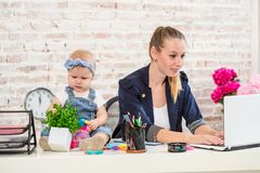 Businesswoman mother woman with a daughter working at the laptop Stock Photography