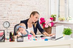 Businesswoman mother woman with a daughter working at the laptop. Businesswoman mother women with a daughter working at the laptop. At the workplace, together Royalty Free Stock Image