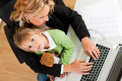 Businesswoman and mother is working at home Stock Image