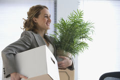 Businesswoman Moves Her Belongings. A young businesswoman smiles as she carries her office belongings in her hands.  Horizontal shot Royalty Free Stock Images