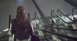 Businesswoman moving downstairs on escalator in the office 4k. Rear view of Businesswoman moving downstairs on escalator in the office. She is looking away 4k stock video