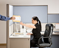 Businesswoman multi-tasking at desk in cubicle Royalty Free Stock Photography