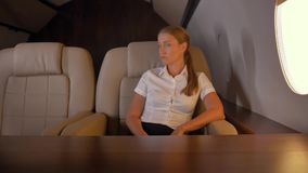 Businesswoman near first class aircraft porthole stock footage