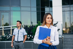 Businesswoman near office on the background of the businessman Stock Photos