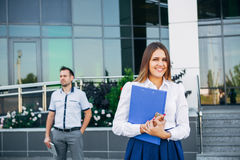 Businesswoman near office on the background of the businessman Stock Image