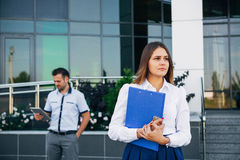 Businesswoman near office on the background of the businessman royalty free stock images