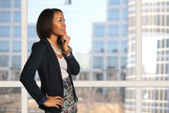 Businesswoman Near Office Window Thinking. African American businesswoman near office building with hand on chin Royalty Free Stock Images