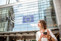 Businesswoman near the parliament building in Brussel. Young businesswoman standing with phone near the Parliament building of European Union in Brussel city stock images