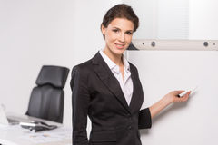 Businesswoman near whiteboard. Royalty Free Stock Image